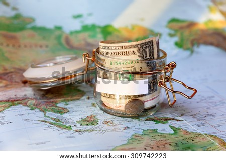 Collecting money for travel. Glass tin as moneybox with cash savings (banknotes and coins) on map as background. White empty space for your text. Moneybox in sunlight. - stock photo