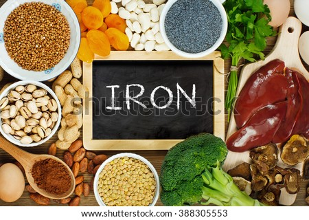 Collection iron rich foods as liver, buckwheat, eggs, parsley leaves, dried apricots, cocoa, lentil, bean, blue poppy seed, broccoli, dried mushrooms, peanuts and pistachios on wooden table. - stock photo