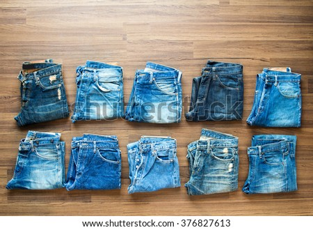 Collection jeans stacked on a wooden background, View from above - stock photo
