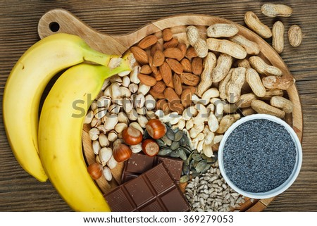 Collection natural products containing magnesium as pumpkin seeds, blue poppy seed, cashew nuts, almonds, sunflower seeds, peanuts, hazelnuts and pistachios  - stock photo