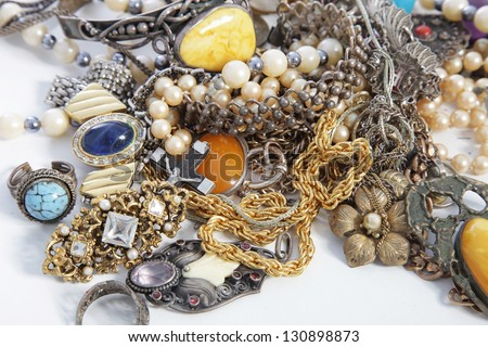 Collection of assorted gemstone jewellery with pearls, necklaces, rings, bracelets and chains in a jumbled pile for a fashion background - stock photo