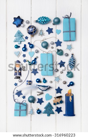 Collection of blue and turquoise miniatures with presents for christmas decoration on wooden white background. - stock photo