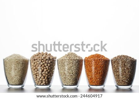 Collection of cereals and legumes in transparent cup on a white background - stock photo
