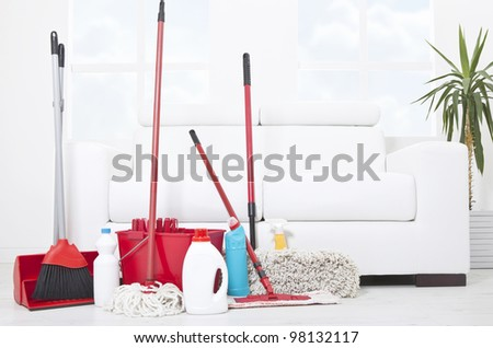 Collection of cleaning products and tools in living room - stock photo