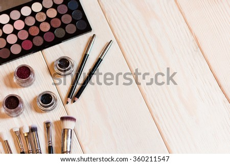 collection of cosmetics for make-up artist. Neutral eye shadows, pigments, glitter, brushes and eyeliner. studio photo on a wooden background with free space. - stock photo