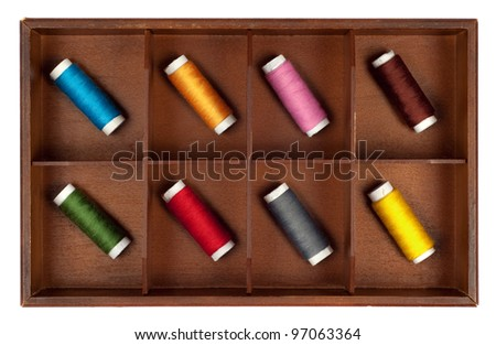 Collection of different color spools of thread  arranged in a grunge wooden box.Isolated on white background - stock photo