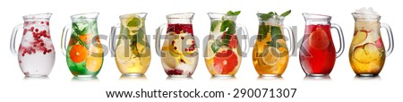 Collection of different drinks in glass pitchers. Jugs full of spritzers, schorle,lemonade,iced tea, detox waters. - stock photo