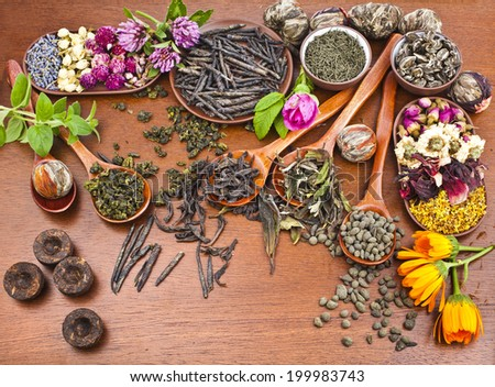 Collection of different dry types tea (green,black, herbal) in wooden spoon on kitchen red wooden table background,  top view - stock photo