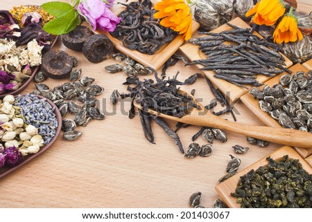 Collection of different dry types tea (green,black, herbal) in wooden spoon on kitchen  wooden table background,  top view - stock photo