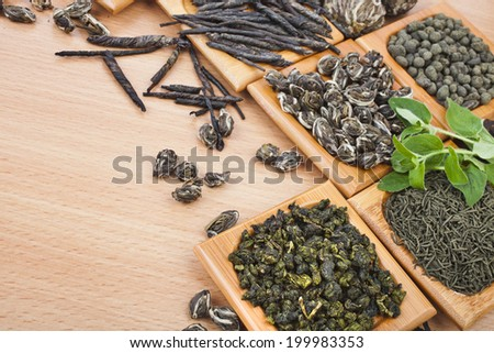 Collection of different dry types tea (green,black, herbal) on kitchen  wooden table background,  top view - stock photo