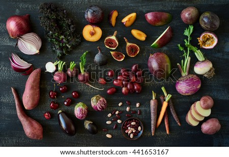 Collection of fresh purple toned vegetables and fruits on dark rustic distressed background, eggplant, turnip, mango, carrot, , radishes, kale, kidney beans, plum, passionfruit, cherries - stock photo