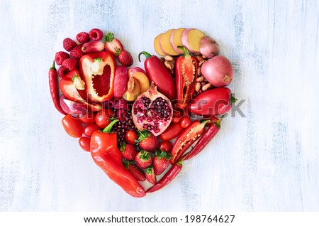 Collection of fresh red vegetables and fruits arranged in a heart shape on white rustic background strawberry raspberry pomegranate peppers capsicum chilli potato beans legumes - stock photo