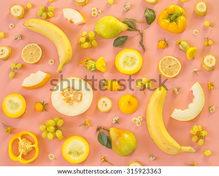 Collection of fresh yellow fruit and vegetables on the light pink background - stock photo