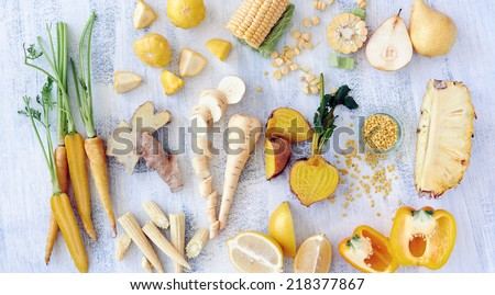 Collection of fresh yellow vegetables and fruits raw produce on white rustic background carrot corn capsicum pineapple pear ginger golden beetroot - stock photo