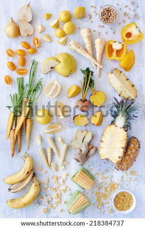 Collection of fresh yellow white toned vegetables and fruits raw produce on white rustic background, capsicum peppers pineapple corn carrot pear quince soy beans legumes lentils ginger parsnip - stock photo