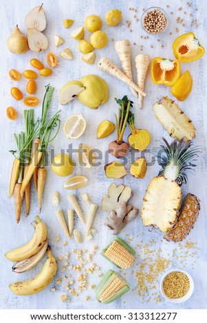 Collection of fresh yellow white toned vegetables and fruits raw produce on white rustic background, capsicum peppers pineapple corn carrot pear quince soya beans legumes lentils ginger parsnip - stock photo