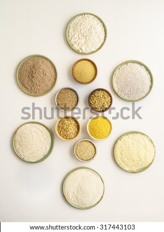 Collection of gluten free grain and flours in small bowls. Clockwise from top amaranth, buckwheat, millet, quinoa, rice, teff - stock photo