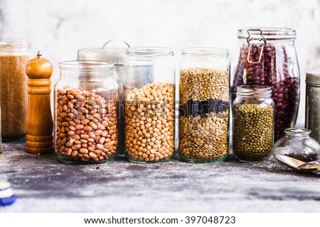 Collection of grain products, lentils, soybeans and red beans in storage jars over on kitchen rural table. - stock photo