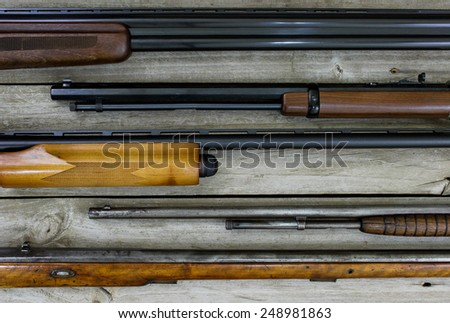Collection of guns lined up horizontal on wooden background - stock photo