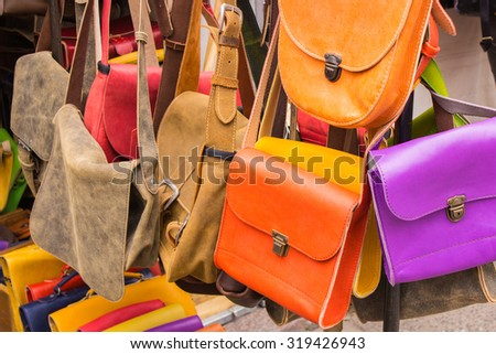Collection of handmade leather handbags on stall at the bazaar, womanly accessories - stock photo