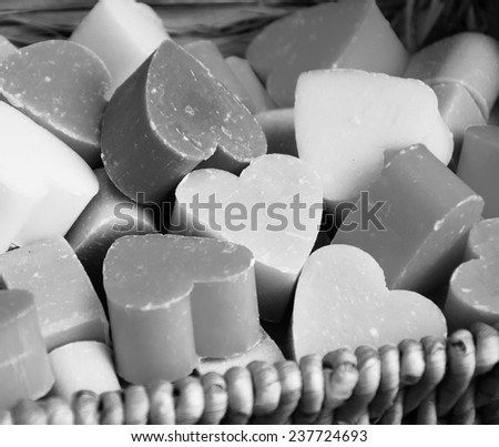 Collection of heart shaped soaps in wicker basket . Aged photo. Black and white. - stock photo