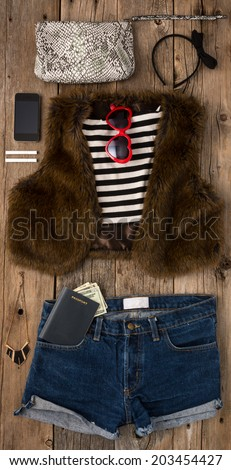 Collection of hip woman's summer clothing with passport ready to travel shot from above - stock photo
