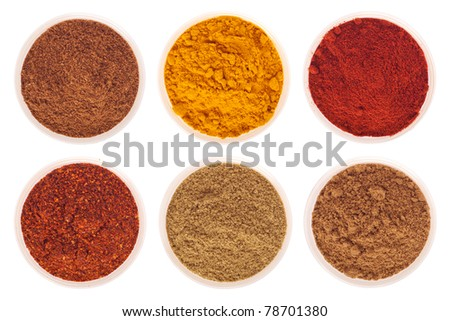 collection of indian spices (cumin, coriander, paprika, garam masala, curcuma, chili powder) on glass cups isolated on white background (shallow DOF, focus on first) - stock photo