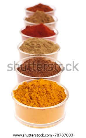 collection of indian spices (cumin, coriander, paprika, garam masala, curcuma, chili powder) on glass cups isolated on white background (shallow DOP, focus on first) - stock photo