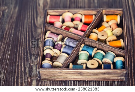 Collection of multicolor pools threads arranged in a grunge wooden box - stock photo