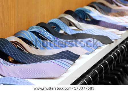 collection of neck ties on shelf in shop, perspective view - stock photo