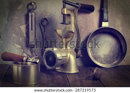 Collection of old kitchen utensils: a mechanical grinder, steel pan, tea strainer, scissors, spring balance, a can opener, a can on a wooden table against a wall with cracked plaster. Tinted photos - stock photo