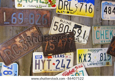 Collection of old vintage American license plates on a wood wall - stock photo