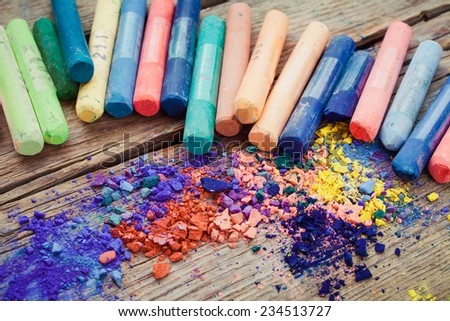 Collection of rainbow colored pastel crayons with pigment dust. - stock photo
