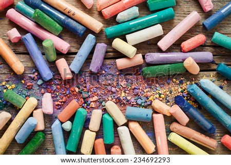 Collection of rainbow colored pastel crayons with pigment dust on old desk. - stock photo