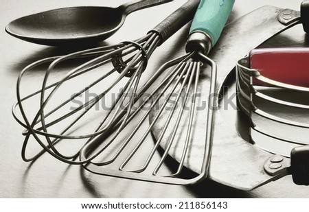 Collection of retro, vintage kitchen utensils. Black and white with original color in wooden handles. - stock photo