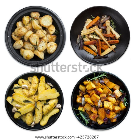 Collection of roasted vegetables on black platters, isolated on white.  Includes potatoes, kumara, parsnips and carrots. - stock photo
