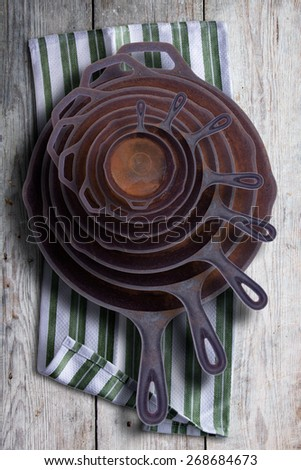 Collection of round rusty cast iron frying pans in diminishing sizes stacked one inside the other, viewed from above on a rustic napkin on an old wooden table - stock photo