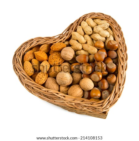 collection of shelled nuts in a heart-shaped basket isolated on white  - stock photo