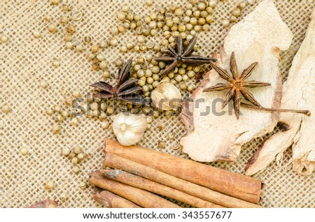 Collection of spices for mulled wine and pastry on sack background. - stock photo
