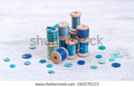 Collection of spools  threads in gree, blue, aqua colors arranged on a white wooden table - stock photo