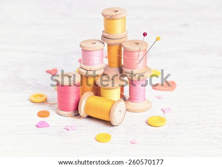 Collection of spools  threads in yellow, pink colors arranged on a white wooden table - stock photo