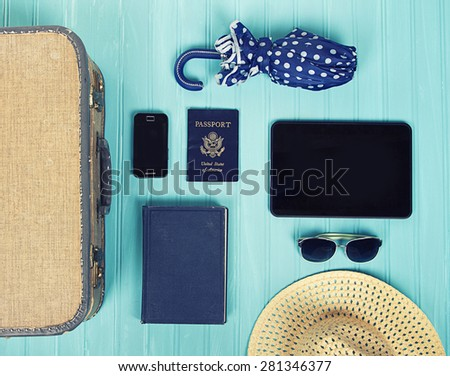 Collection of vacation travel items with a vintage filter on a turquoise background - stock photo