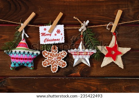 collection of various christmas stars with greeting card hanging on twine against wooden background - stock photo