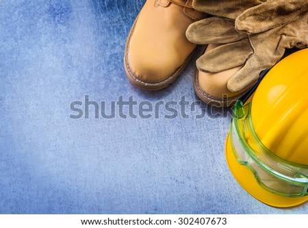 Collection of waterproof boots protective leather gloves building helmet and safety glasses on scratched metallic surface construction concept. - stock photo