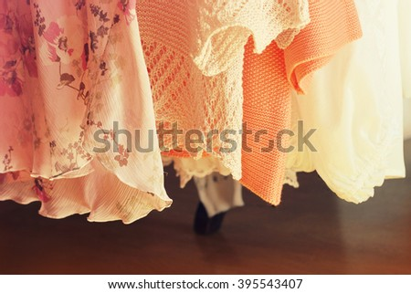 collection of women's clothes hanging on a rack  - stock photo