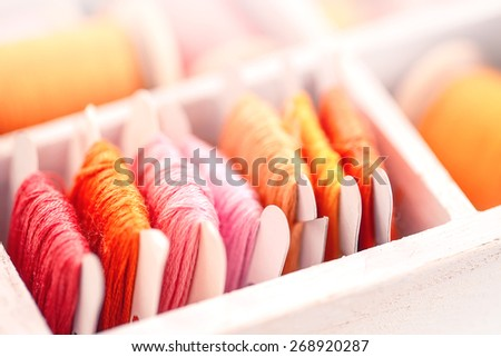 Collection of yellow, red, pink spools  threads on in a white wooden box - stock photo