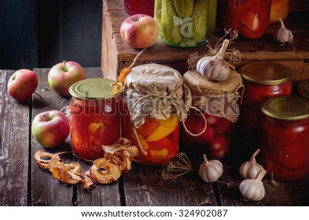 Collection set of many homemade glass jars with preserved food (cucumbers, tomatoes, peppers), with garlic and fresh and dried apples. Over old wooden table. Dark rustic style - stock photo