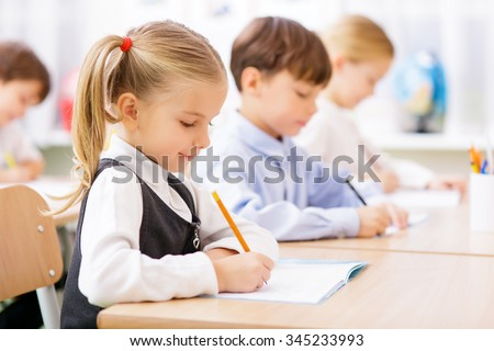 Collective work. Little pupils are all busy writing in their copybooks. - stock photo