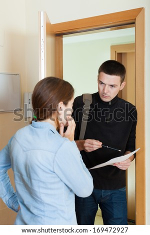 collector  trying to get the arrears from woman at home door - stock photo