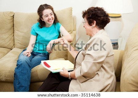 College admissions counselor or therapist interviews teen student.  It's going well. - stock photo